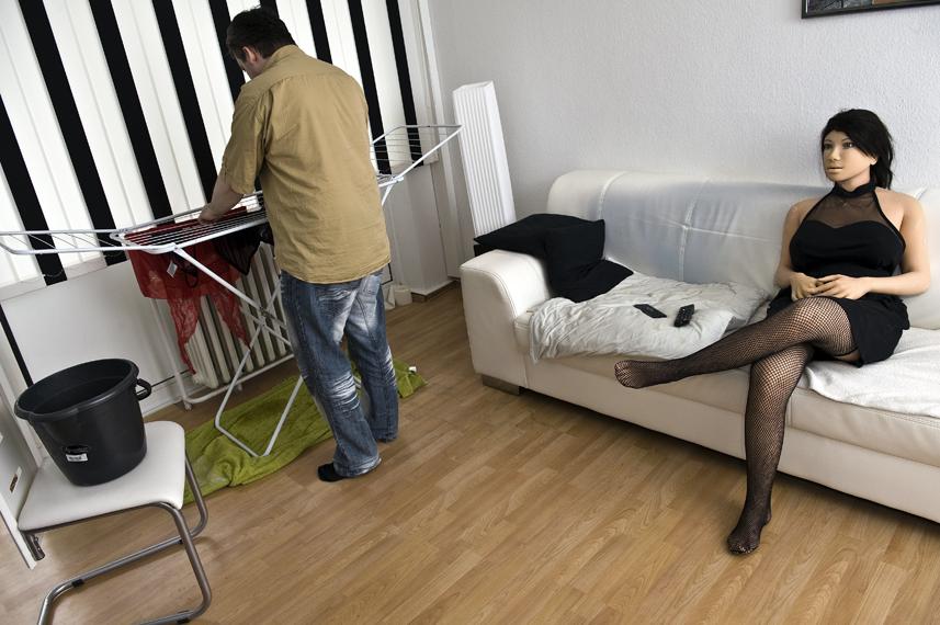 Jenny sitzt im Wohnzimmer auf dem Sofa, Dirk hŠngt ihre WŠsche auf.