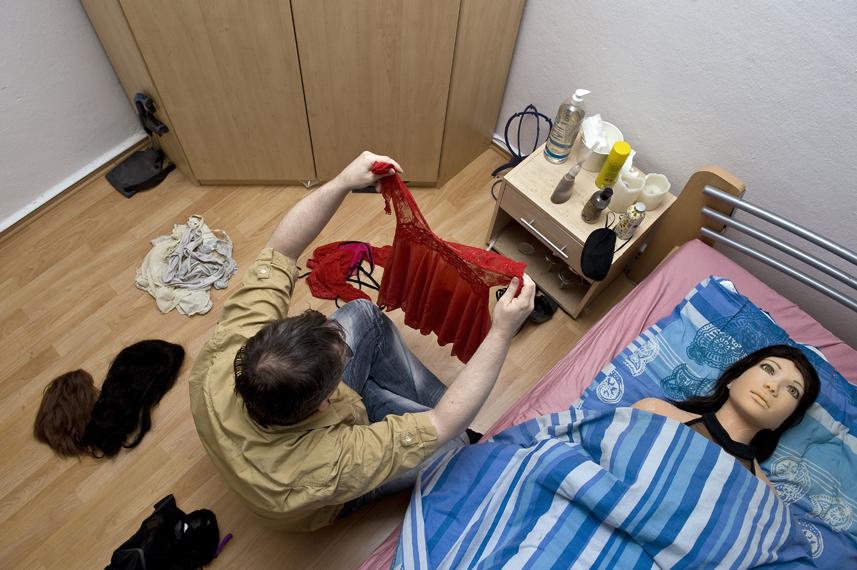 Dirk sortiert im Schlafzimmer Jennys dreckige WŠsche. Jenny liegt im Bett. Jeden Sonntag wŠscht Dirk ihre SpitzenwŠsche und PerŸcken.