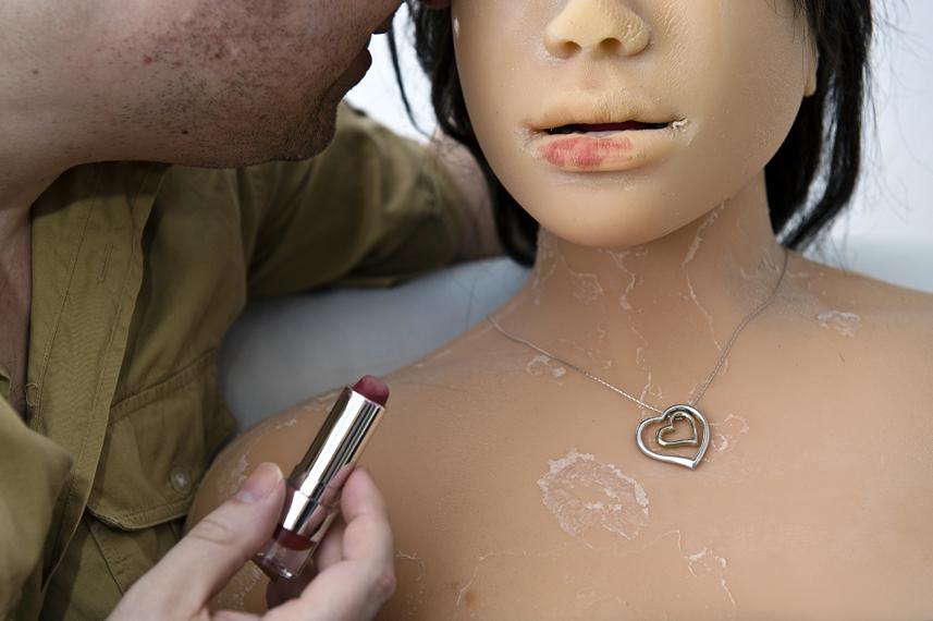 Dirk schminkt Jenny ihre Lippen. Sie trŠgt die Herzkette um den Hals, die Dirk ihr zur Hochzeit geschenkt hat, weil ein Ring nicht Ÿber ihre weichen Silikon-Finger passt.