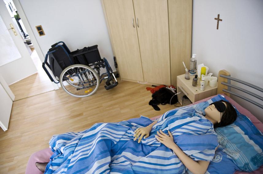 Jenny liegt mit Schlafbrille im Bett. Sie muss sich tagsŸber oft ausruhen. An der Wand hŠngt ein Kreuz, Jenny glaubt an Gott und betet jeden Tag.