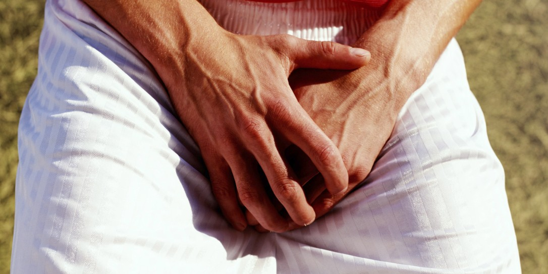Man covering groin with hands, outdoors, close-up